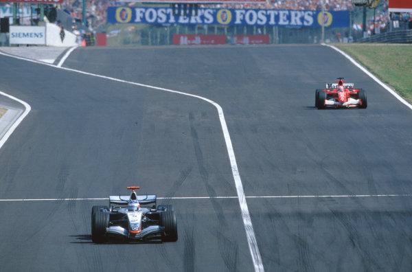 2005 Hungarian Grand Prix. Hungaroring, Hungary. 29th - 31st July 2005 Kimi Raikkonen, McLaren Mercedes MP4-20 leads Michael Schumacher, Ferrari F2005. Action. World Copyright: Charles Coates/LAT Photographic Ref: 35mm Image A29