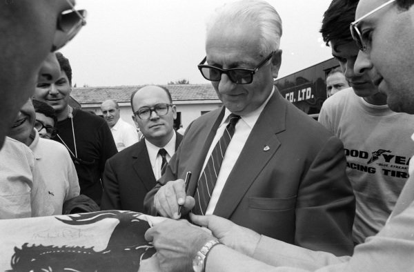 Enzo Ferrari signs autographs in the paddock.