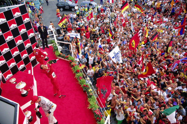 Michael Schumacher celebrates on the podium with David Coulthard in front of a pitlane full of fans.