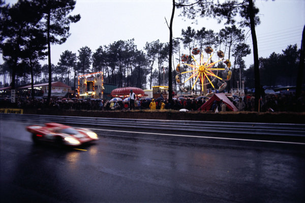 The funfair in full swing with the Richard Attwood / Hans Herrmann Porsche 917K in the foreground.