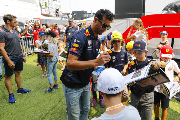 Daniel Ricciardo, Red Bull Racing, signs autographs for young fans as Romain Grosjean, Haas F1 Team, looks on.
