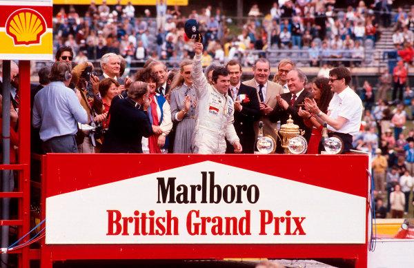 1980 British Grand Prix.Brands Hatch, England.11-13 July 1980.Alan Jones (Williams Ford) 1st position celebrates on the podium. Ref-80 GB 22.World Copyright - LAT Photographic