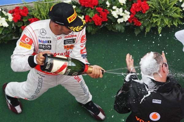 Race winner Lewis Hamilton (GBR) McLaren celebrates on the podium with Simon Roberts (GBR) McLaren Operations Director. Formula One World Championship, Rd 10, German Grand Prix, Race, Nurburgring, Germany, Sunday 24 July 2011.  BEST IMAGE