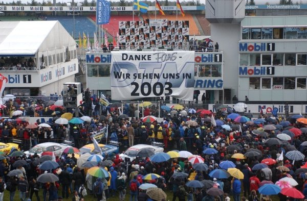 "DTM Championship 2002, Round 10 - Hockenheimring, Germany, 6 October 2002 - DTM Championship 2002, Round 10 - Hockenheimring, Germany, 6 October 2002 - Drivers and teams thank the fans by unfolding a big banner with the message ""Thanks fans, we'll see each other again in 2003""."