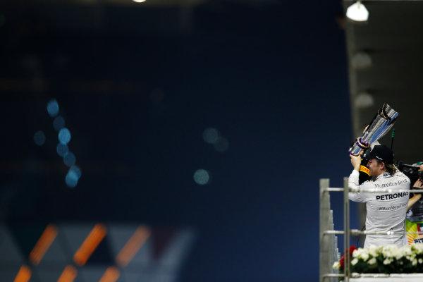 Yas Marina Circuit, Abu Dhabi, United Arab Emirates. Sunday 29 November 2015. Nico Rosberg, Mercedes AMG, 1st Position, lifts his trophy on the podium. World Copyright: Charles Coates/LAT Photographic ref: Digital Image _99O2803