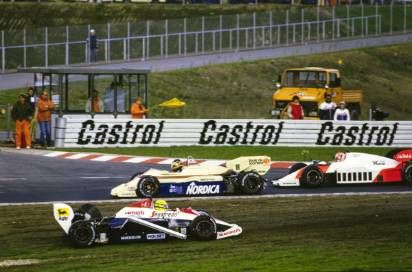 Thierry Boutsen, Arrows A7 BMW, and Niki Lauda, McLaren MP4-2 TAG, pass the wrecked Ayrton Senna, Toleman TG184 Hart.