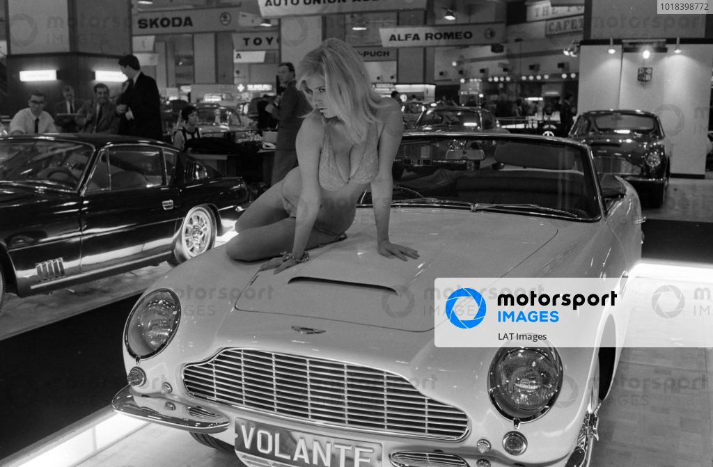 A model poses on the bonnet of an Aston Martin DB6 Volante.