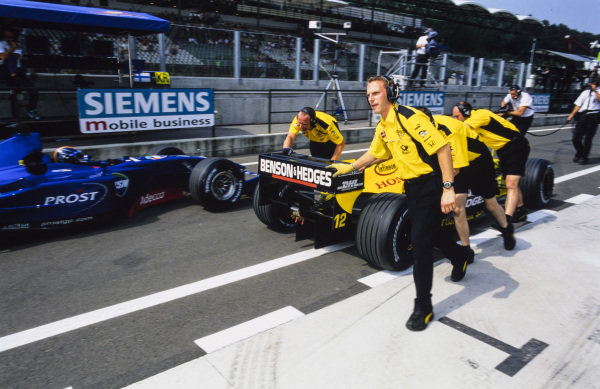 Jean Alesi, Jordan EJ11 Honda, is pushed down the pitlane as Heinz-Harald Frentzen, Prost AP04 Acer, drives past. The pair swapped seats ahead of the weekend.