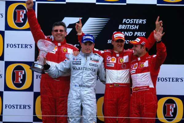 2004 British Grand Prix Silverstone England. 9th - 11th July. Michael Schumacher, Ferrari F2004 , Kimi Raikkonen, McLaren Mercedes MP4/19 , Rubens Barrichello, Ferrari F2004 and Ross Brawn, Ferrari celebrate on the podium. World Copyright:Peter Spinney/LAT Photographic  Ref:35mm image A24