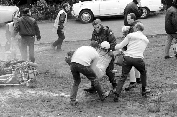 """Medical """"experts"""" manhandle the unfortunate Brian Redman (GBR) from his wrecked Cooper T86B. He suffered a badly broken arm that saw him out of F1 for two seasons.  Belgian Grand Prix, Spa-Francorchamps, June 9 1968."""