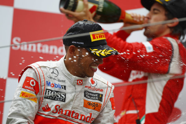 Nurburgring, Germany.24th July 2011Lewis Hamilton, McLaren MP4-26 Mercedes, 1st position, and Fernando Alonso, Ferrari 150° Italia, 2nd position, spray the Champagne. Portrait. Podium. World Copyright: Andy Hone/LAT Photographicref: Digital Image CSP13514