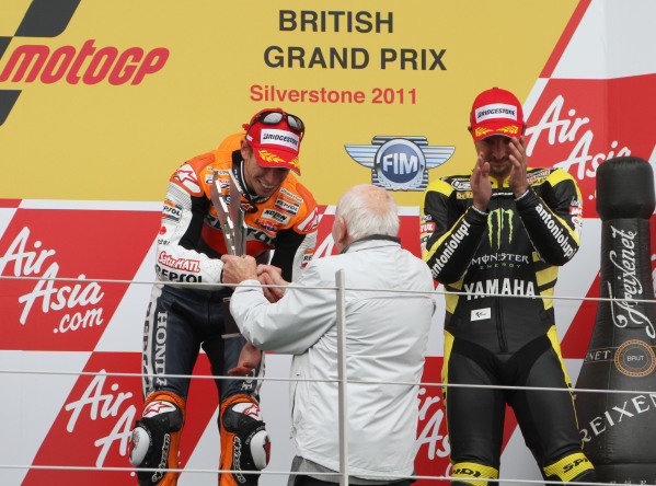 British Grand Prix. Silverstone, England. 10th-12th June 2011. Casey Stoner, Honda, receives the winner's trophy from John Surtees on the podium as Colin Edwards applauds. World Copyright: Kevin Wood/LAT Photographic. ref: Digital Image