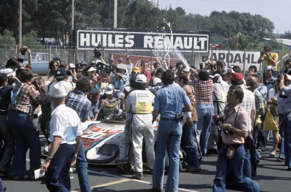 1976 Le Mans 24 hours. Le Mans, France. 12-13 June 1976. Jacky Ickx/Gijs van Lennep (Porsche 936), 1st position. Mechanics, fans and marshals greet the winners with champagne. World Copyright: LAT Photographic Ref: 76LM04