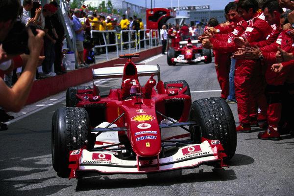 Michael Schumacher, Ferrari F2004 pulls into parc ferme where his team celebrate victory.