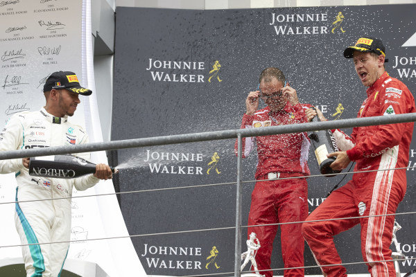 Lewis Hamilton, Mercedes AMG F1, 2nd position, David Sanchez, Principal Aerodynamicist, Ferrari, and Sebastian Vettel, Ferrari, 1st position, celebrate on the podium with Champagne.