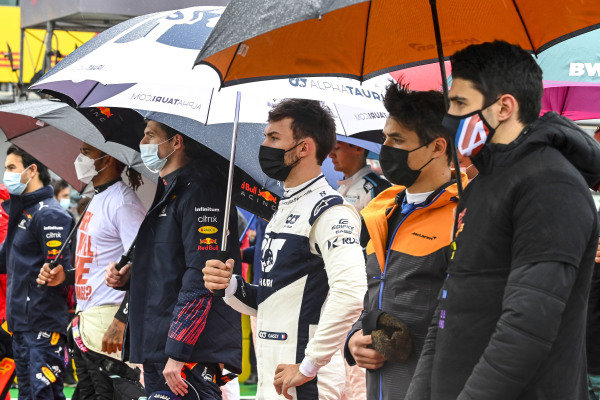 Max Verstappen, Red Bull Racing, Pierre Gasly, AlphaTauri, Lando Norris, McLaren, Esteban Ocon, Alpine F1, and the other drivers stand for the national anthem prior to the start
