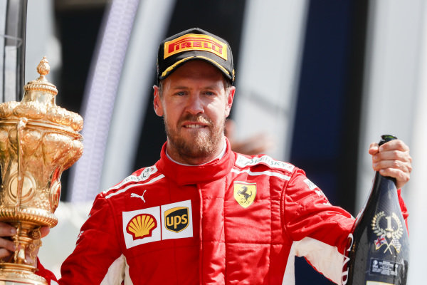 Sebastian Vettel, Ferrari, 1st position, with his trophy and Champagne.