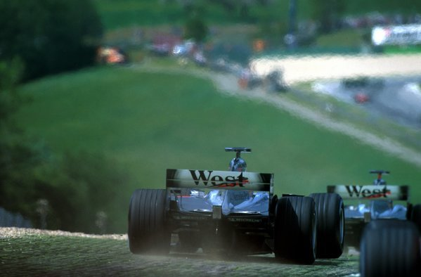 The McLarens run wide at the first corner.
