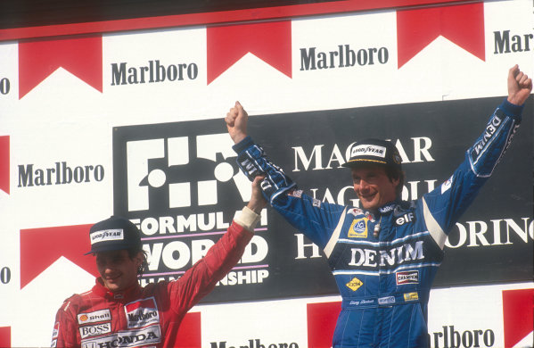 1990 Hungarian Grand Prix.Hungaroring, Budapest, Hungary.10-12 August 1990.Ayrton Senna (McLaren Honda) 2nd position congratulates Thierry Boutsen (Williams Renault) 1st position on the podium.Ref-90 HUN 03.World Copyright - LAT Photographic