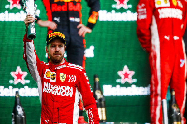 Sebastian Vettel, Ferrari, 2nd position, holds up his trophy on the podium