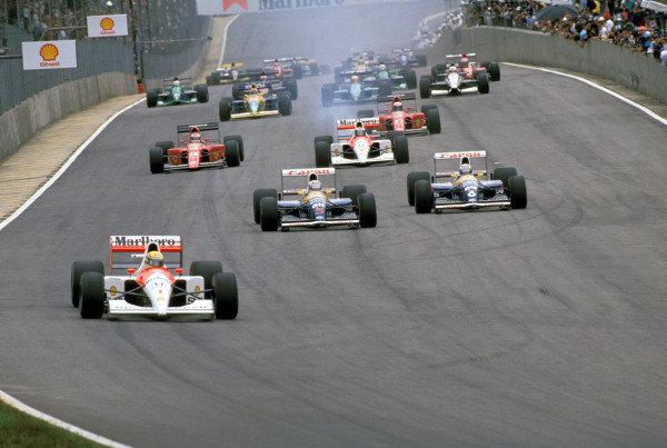 Ayrton Senna, McLaren MP4-6 Honda, leads Nigel Mansell, Williams FW14 Renault, Riccardo Patrese, Williams FW14 Renault, Gerhard Berger, McLaren MP4-6 Honda, Jean Alesi, Ferrari 642, and Alain Prost, Ferrari 642, at the start of the race.