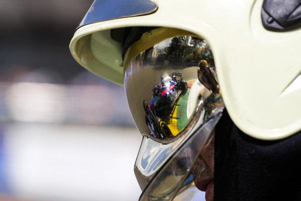 Daniil Kvyat, Toro Rosso STR14, is reflected in a fire marshal's visor