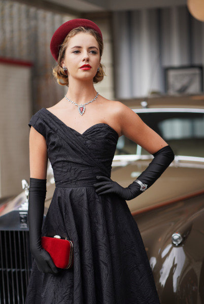 A model in 1950s period fashion poses during a photoshoot with a Rolls Royce.