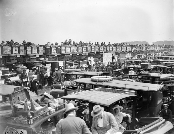 Rows of coaches and bookmakers amongst crowds and vehicles at the Epsom Derby