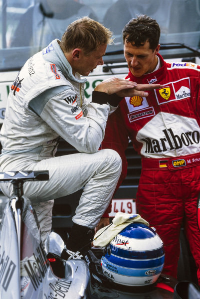 Mika Häkkinen, 1st position, and Michael Schumacher, 2nd position, discuss the race in Parc Ferme. Häkkinen was unimpressed with the manoeuvre Schumacher made on-track late into the race and expressed his views on it.