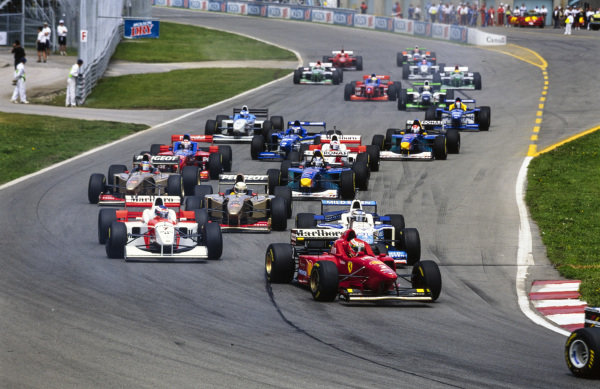Eddie Irvine, Ferrari F310 leads Gerhard Berger, Benetton B196 Renault, and Mika Häkkinen, McLaren MP4-11 Mercedes, as the rest of the pack follows at the start of the race.