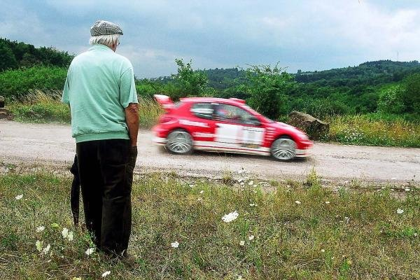 A spectator watches Marcus Gronholm (FIN), Peugeot 206 WRC.World Rally Championship, Rd8, Rallye Deutschland, Trier, Germany. 23-27 July 2003.DIGITAL IMAGE
