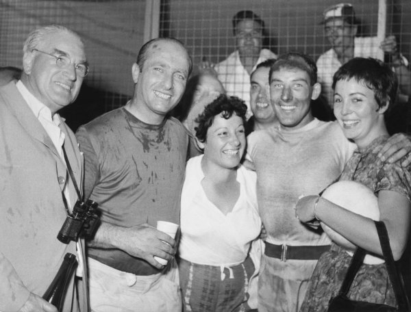 Monza, Italy. 6-8 September 1957.Juan Manuel Fangio (Maserati 250F), 2nd position, celebrates with his wife, Senora Fangio and winner Stirling Moss (Vanwall), 1st position with his fiancee, Katie Molson in the pits, portrait.World Copyright : LAT PhotographicRef : Autocar Used Pic 13th September 1957 Page 357