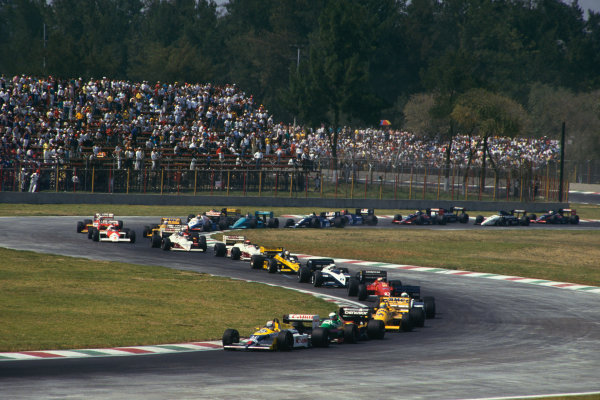 Mexico City, Mexico. 16-18 October 1987. Nigel Mansell (Williams FW11B Honda) 1st position, leads Teo Fabi (Benetton B187 Ford), Ayrton Senna (Lotus 99T Honda) and the rest of the field on the first lap. Ref: 87 MEX 09. World Copyright - LAT Photographic