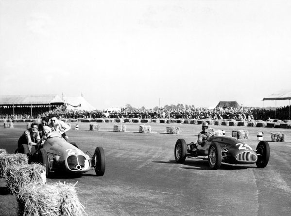"1950 British Grand Prix.Silverstone, Great Britain. 13th May 1950.Geoffrey Crossley (Alta GP) passes the retiring ""B Bira"" (Maserati 4CLT/48).World Copyright: LAT Photographicref: B&W Print"