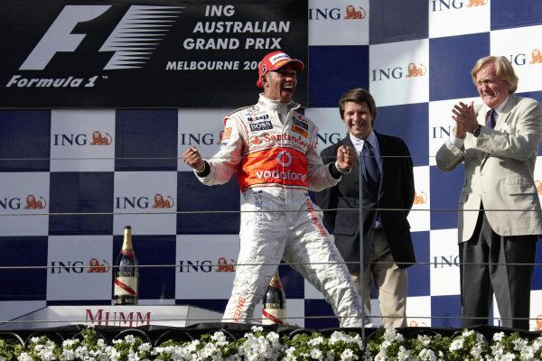Lewis Hamilton celebrates victory on the podium.