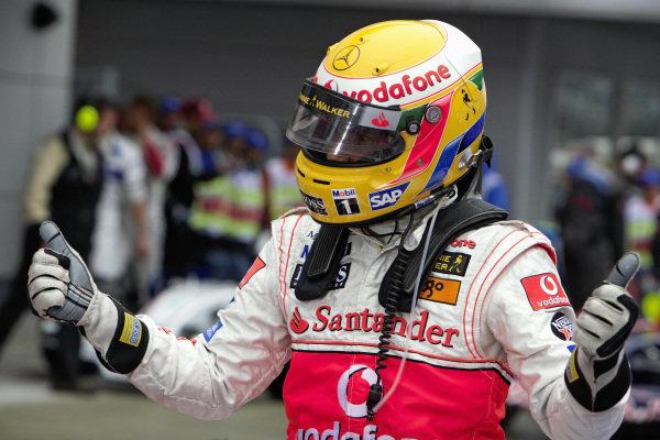 Lewis Hamilton celebrates claiming pole position in parc fermé.