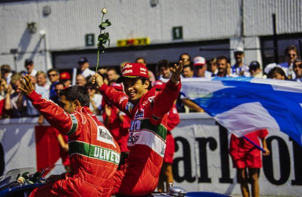 Christian Fittipaldi holds a rose alongside team-mate Gianni Morbidelli on the drivers' parade.