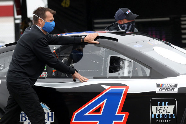 Crew members push the car of Kevin Harvick, Stewart-Haas Racing Mobil 1 Ford  through the garage area, Copyright: Chris Graythen/Getty Images.