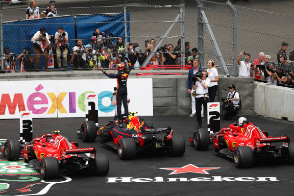 Max Verstappen, Red Bull Racing, 1st position, celebrates on arrival in Parc Ferme, as Kimi Raikkonen, Ferrari, 3rd position, and Sebastian Vettel, Ferrari, 2nd position, park their cars