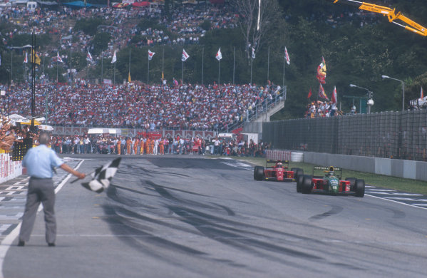 1990 San Marino Grand Prix.Imola, Italy.11-13 May 1990.Alessandro Nannini (Benetton B190 Ford) takes the chequered flag for 3rd position closely followed by Alain Prost (Ferrari 641) 4th position.Ref-90 SM 08.World Copyright - LAT Photographic