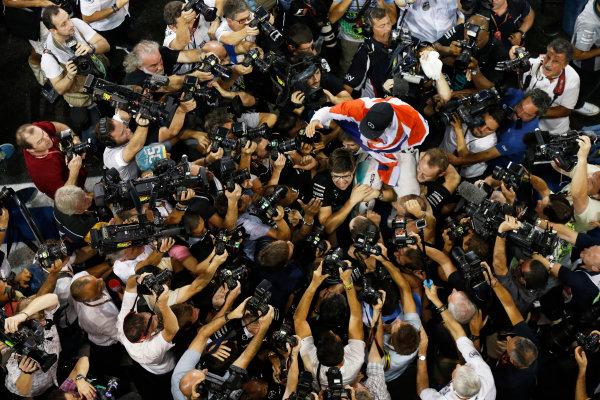 Yas Marina Circuit, Abu Dhabi, United Arab Emirates. Sunday 23 November 2014. Lewis Hamilton, Mercedes AMG, 1st Position, celebrates with his team. World Copyright: Charles Coates/LAT Photographic. ref: Digital Image _J5R7456