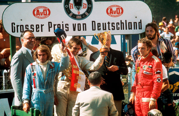 1975 German Grand Prix.Nurburgring, Germany.1-3 August 1975.Carlos Reutemann (Brabham BT44B-Ford) 1st position, Jacques Laffite (Williams FW04-Ford) 2nd position and Niki Lauda (Ferrari 312T) 3rd position, on the podium, portrait. 