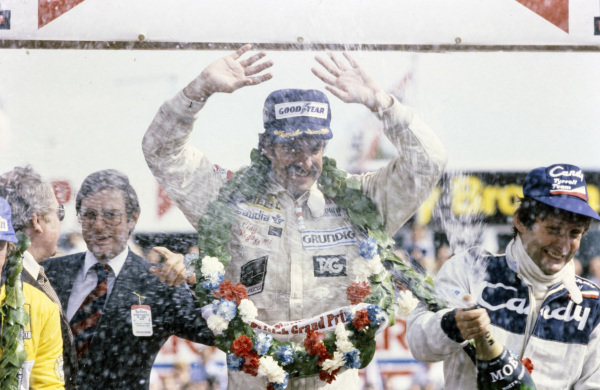 Jean-Pierre Jarier, 3rd position, sprays champagne on the podium as Clay Regazzoni celebrates his victory.