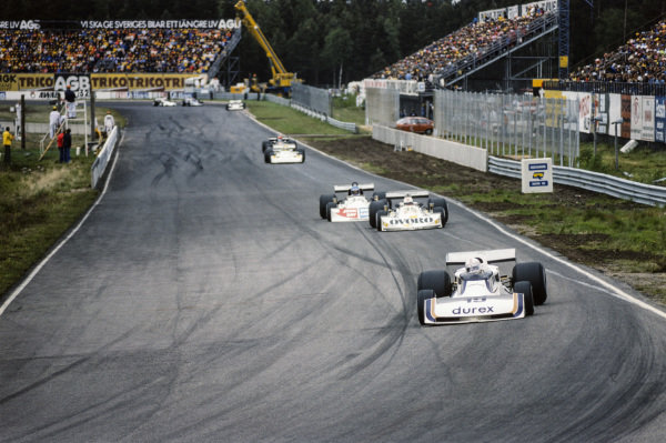 Alan Jones, Surtees TS19 Ford leads Arturo Merzario, March 761 Ford and Hans-Joachim Stuck, March 761 Ford.