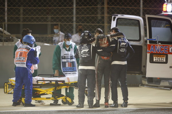 Romain Grosjean, Haas F1, is assisted by medical delegates and marshals after a big crash on the opening lap
