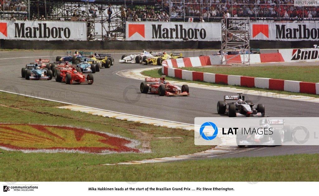 1998 Brazilian Grand Prix.Interlagos, Sao Paulo, Brazil.27-29 March 1998.Mika Hakkinen (McLaren MP4/13 Mercedes-Benz) leads at the start. He finished in 1st position.World Copyright - Steve Etherington/LAT Photographic