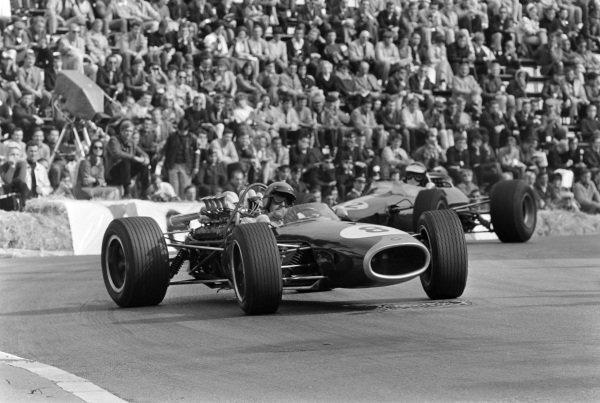 Jack Brabham, Brabham BT19 Repco, corrects a slide ahead of Jim Clark, Lotus 33 Climax.