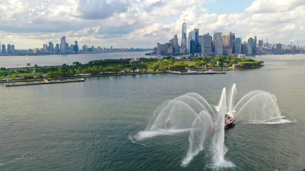 An FDNY Fire Tender sprays its hoses in the Hudson River after the race