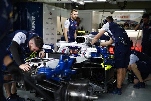 Mechanics work on the Sergey Sirotkin Williams FW41 Mercedes in the team's garage.