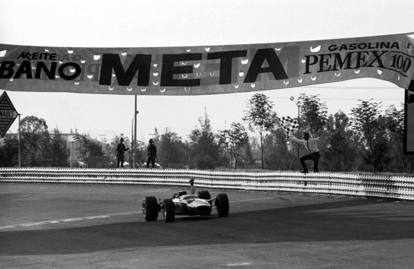 Jim Clark (GBR) Lotus 49 celebrates as he takes the chequered flag and race victory.  Mexican Grand Prix, Mexico City, 22 October 1967.